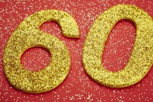 Number sixty golden color over a red background. Anniversary. Horizontal