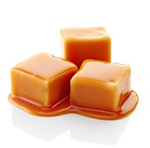 caramel candies and caramel sauce on a white background